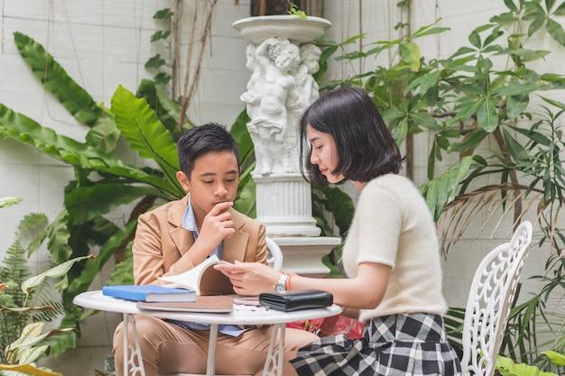 Młoda siostra nauczania pracę domową do młodszego brata uwagę do słuchania