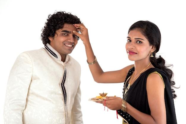 Młoda siostra z indii wiąże rakhi na nadgarstku brata, tradycja na festiwalu raksha bandhan
