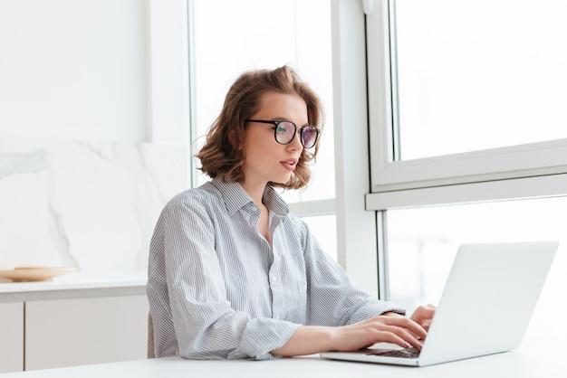 Młoda skoncentrowana kobieta w pasiastej koszuli za pomocą laptopa, siedząc przy stole w lekkim mieszkaniu