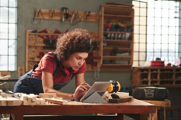 Młoda skoncentrowana kobieta z kręconymi włosami, czytanie instrukcji na tablecie cyfrowym przed rozpoczęciem pracy z drewnem
