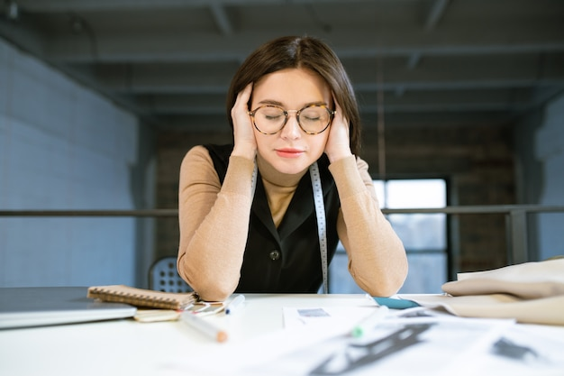 Młoda skoncentrowana lub zmęczona projektantka dotyka głowy podczas pracy nad nową kolekcją mody w studio