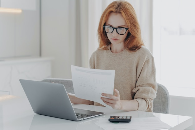 Młoda skupiona rudowłosa kobieta siedzi przy stole z laptopem i trzyma papierowe rachunki podatkowe