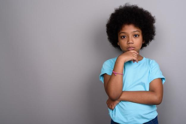 Młoda śliczna afrykańska dziewczyna przeciw szarej ścianie