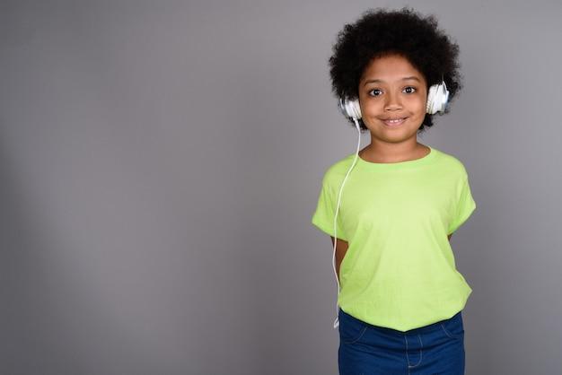 Młoda śliczna afrykańska dziewczyna słucha muzyki na szarej ścianie