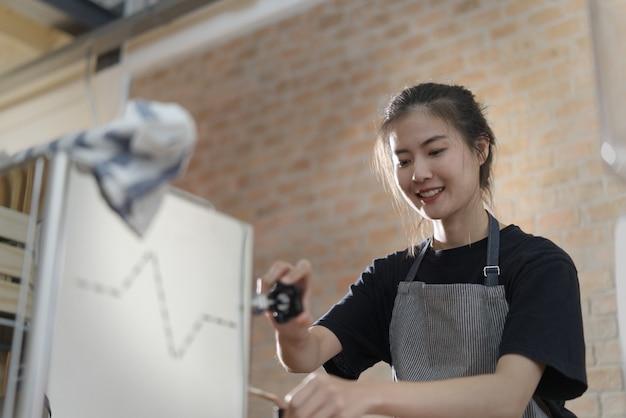 Młoda śliczna azjatycka barista dziewczyna robi kawie w sklep z kawą.