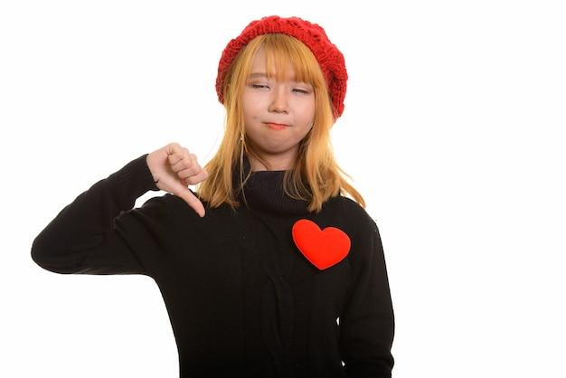 Młoda śliczna azjatycka kobieta daje kciuk w dół z czerwonym sercem na piersi