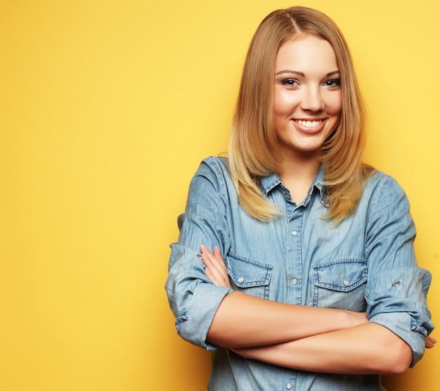 Młoda śliczna blond dziewczyna nad kolor żółty ścianą