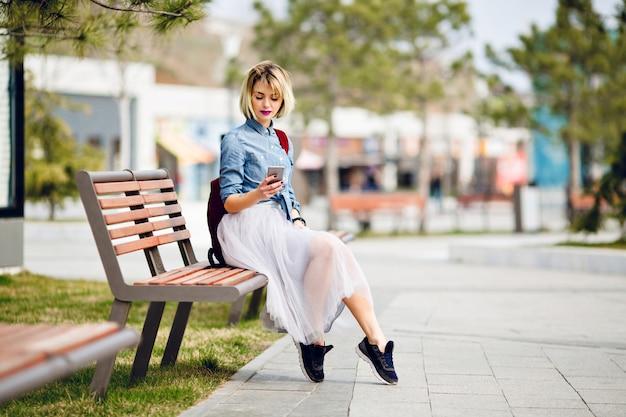 Młoda śliczna blond kobieta z krótkimi włosami i jasnoróżowymi ustami siedzi na drewnianej ławce i czyta wiadomość na smartfonie