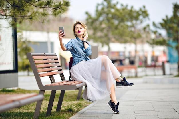 Młoda śliczna blond kobieta z krótkimi włosami i jasnoróżowymi ustami siedzi na drewnianej ławce, robiąc selfie całując usta