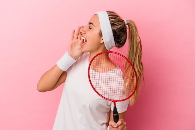 Młoda śliczna blondynka kaukaska kobieta trzyma rakietę do badmintona na białym tle na różowym tle krzycząc i trzymając dłoń w pobliżu otwartych ust.