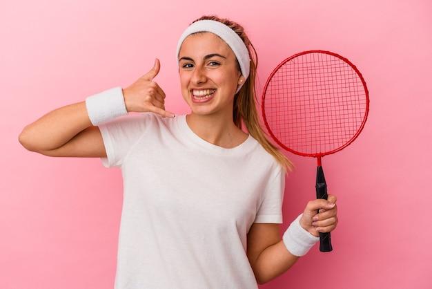 Młoda śliczna blondynka kaukaska kobieta trzyma rakietę do badmintona na białym tle na różowym tle, pokazując gest rozmowy telefonicznej z palcami.