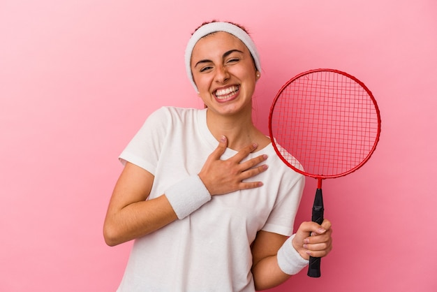 Młoda śliczna blondynka kaukaski kobieta trzyma rakietę do badmintona na białym tle na różowym tle śmieje się głośno, trzymając rękę na piersi.