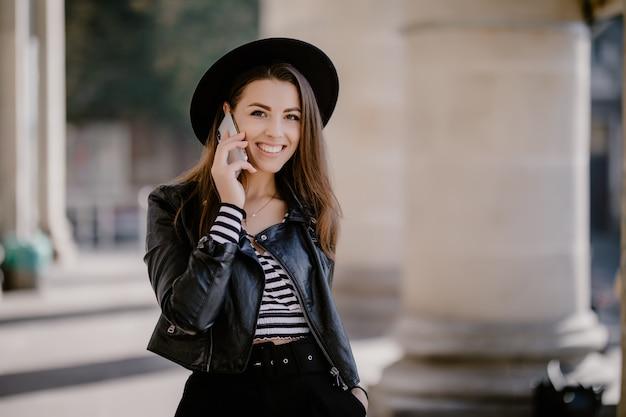 Młoda śliczna brązowowłosa dziewczyna w skórzanej kurtce, czarnym kapeluszu na miejskiej promenadzie prowadzi rozmowę telefoniczną