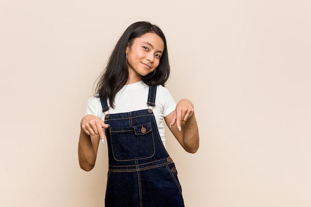Młoda śliczna chińska nastolatka młoda blondynki kobieta jest ubranym żakiet przeciw różowemu tłu wskazuje palcami w dół, pozytywny uczucie.