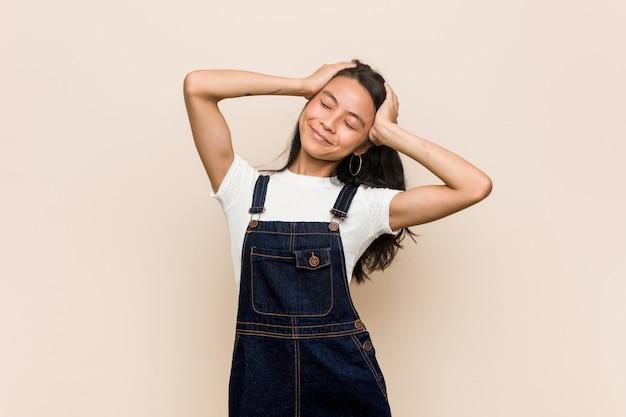 Młoda śliczna chińska nastolatka młoda blondynki kobieta w płaszczu na różowej ścianie śmieje się radośnie trzymając ręce na głowie. koncepcja szczęścia.
