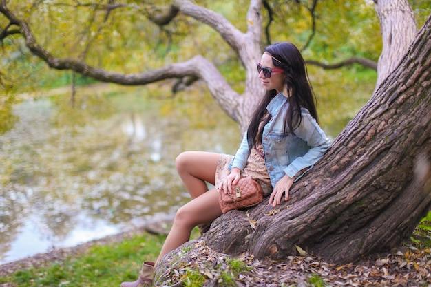 Młoda śliczna dziewczyna cieszy się wakacje w jesień parku blisko jeziora