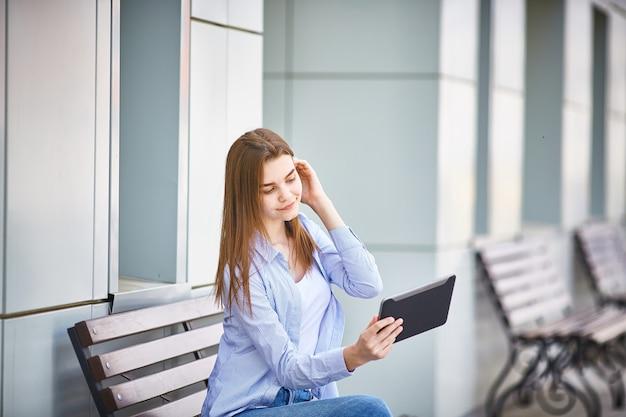 Młoda śliczna dziewczyna opowiada na skype z pastylką na ulicie.