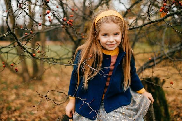Młoda śliczna dziewczyna pozuje w jesiennym parku