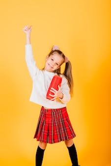Młoda śliczna dziewczyna uśmiecha się i tańczy z bezprzewodowym głośnikiem przenośnym