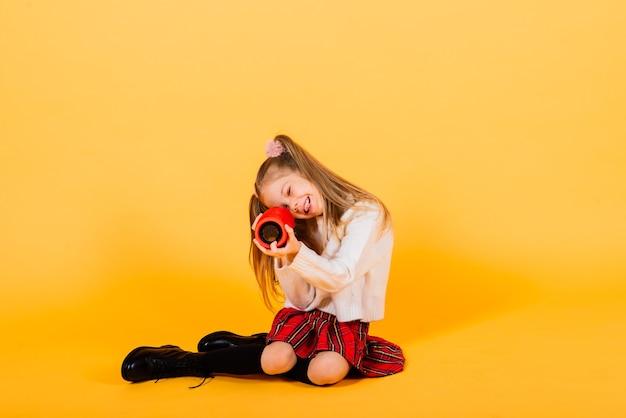 Młoda śliczna dziewczyna uśmiecha się z bezprzewodowym głośnikiem przenośnym
