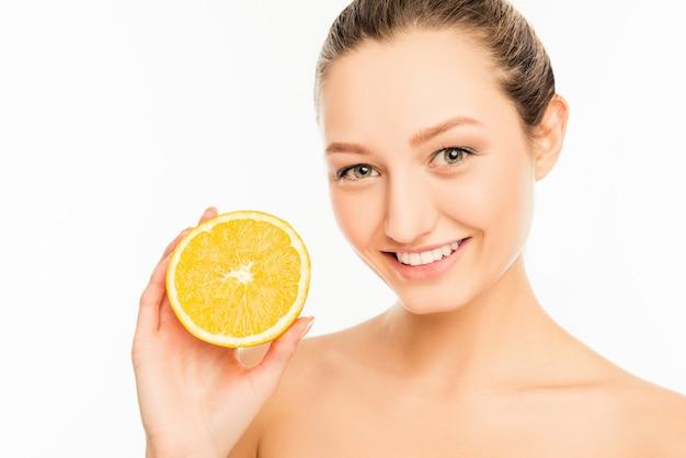 Młoda śliczna dziewczyna z ładnym uśmiechem i plasterek pomarańczy