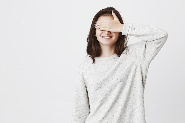 Młoda śliczna europejka, zakrywająca oczy ręką, uśmiechając się wesoło, niecierpliwa.