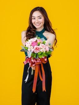 Młoda śliczna i całkiem kręcone włosy azjatycka brunetka trzyma bukiet kwiatów z wesołą i szczęśliwą, studio strzał na białym tle na jasnożółtym tle.