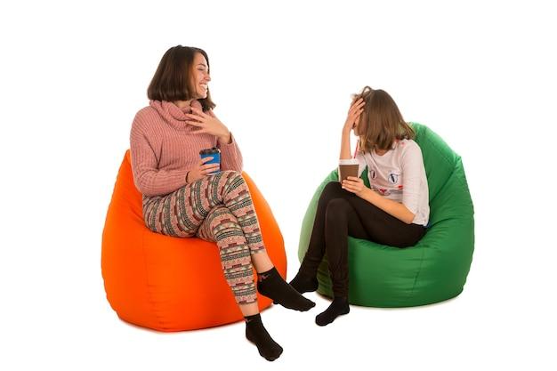Młoda śliczna kobieta i roześmiana dziewczyna siedzi na krzesłach beanbag i pije kawę na białym tle