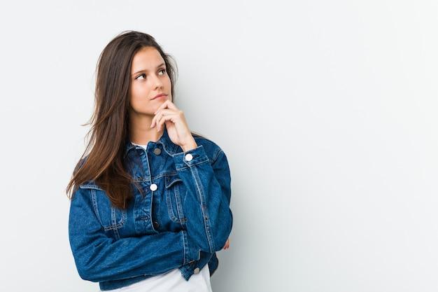 Młoda śliczna kobieta patrzeje z ukosa z wątpliwym i sceptycznym wyrażeniem.