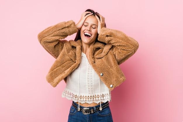 Młoda śliczna kobieta śmieje się radośnie, trzymając ręce na głowie. koncepcja szczęścia.