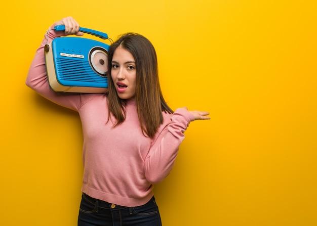 Młoda śliczna kobieta trzyma rocznika radia mienia coś na palmowej ręce