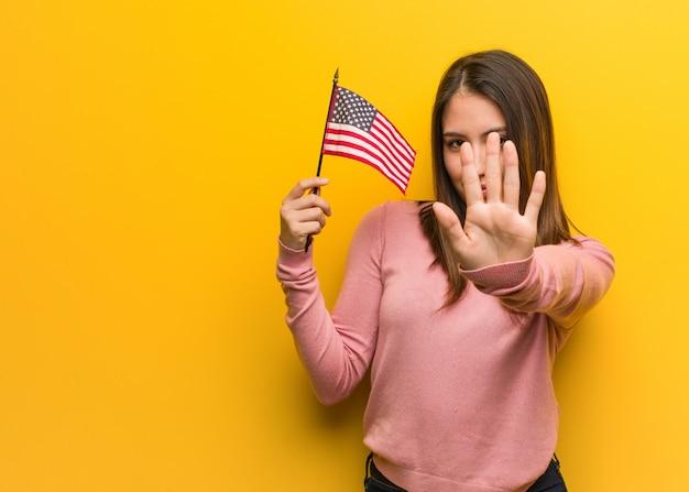 Młoda śliczna kobieta trzyma stany zjednoczone flaga kładzenia rękę w przód