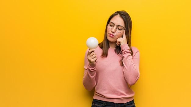 Młoda śliczna kobieta trzyma żarówkę myśleć o pomysle