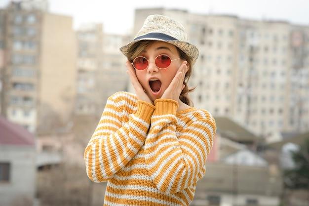 Młoda śliczna kobieta w czapce i okularach pozuje na zewnątrz.