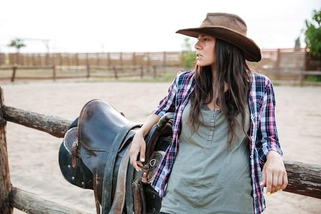 Młoda śliczna kowbojka opierając się na płocie rancza i odwracając wzrok