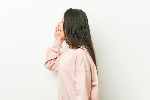 Młoda śliczna latynoska nastolatek kobieta krzyczy palmowego pobliskiego usta i trzyma.