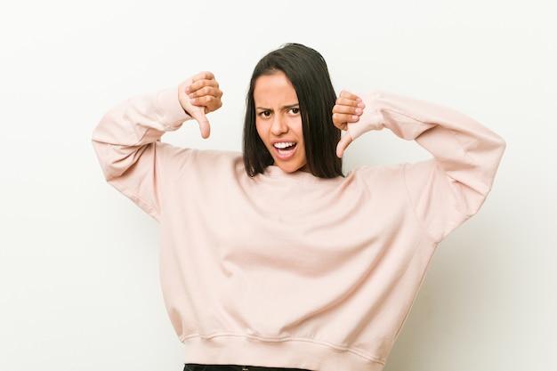 Młoda śliczna latynoska nastolatek kobieta pokazuje kciuka puszek i wyraża niechęć.