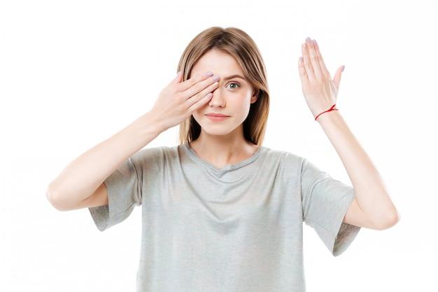 Młoda śliczna młoda kobieta zakrywa oczy