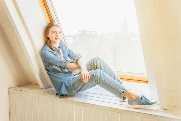 Młoda śliczna nastoletnia dziewczyna siedzi w domu w cajgach