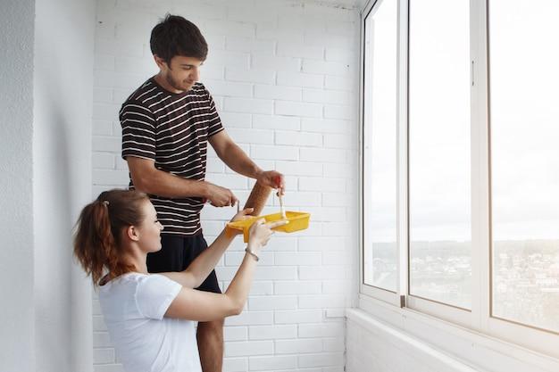 Młoda śliczna para podczas remontu w nowym budynku. facet z brodą traktuje wałkiem białą ścianę, żona daje mu żółtą tacę z farbą.