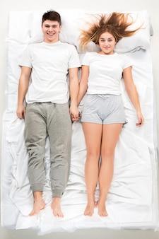 Młoda śliczna para w białym łóżku, uwielbiam koncepcję, widok z góry