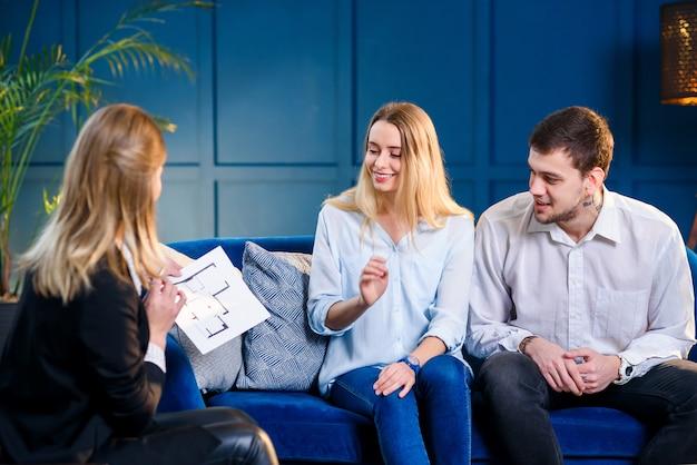 Młoda śliczna rodzina na spotkaniu z pośrednikiem handlu nieruchomościami, projektantem wnętrz, dekoratorem.