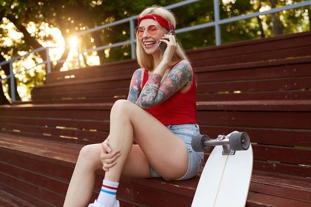 Młoda śliczna, roześmiana blondynka z wytatuowanymi ramionami, rozmawiająca ze swoim przyjacielem na smartfonie, słyszy zabawny żart. nosi czerwoną koszulkę, dżinsowe szorty, na głowie dzianinową bandanę, czerwone okulary.