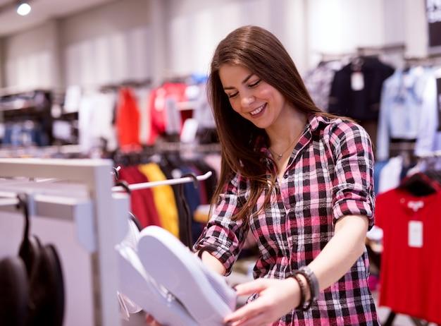 Młoda śliczna szczęśliwa dziewczyna trzyma trampki, które znalazła w sklepie z odzieżą, który naprawdę lubi.