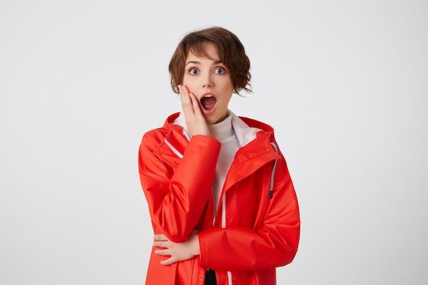 Młoda śliczna, szczęśliwa, zdumiona, krótkowłosa dziewczyna w białym golfie i czerwonym płaszczu przeciwdeszczowym, patrząc z szeroko otwartymi ustami, dotyka policzka, słyszy niewiarygodne wieści. na stojąco.