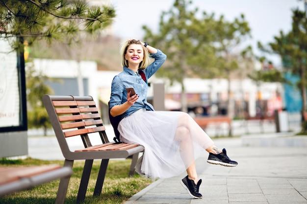 Młoda śliczna uśmiechnięta blond kobieta z krótkimi włosami i jasnoróżowymi ustami siedzi na drewnianej ławce trzymając smartfon