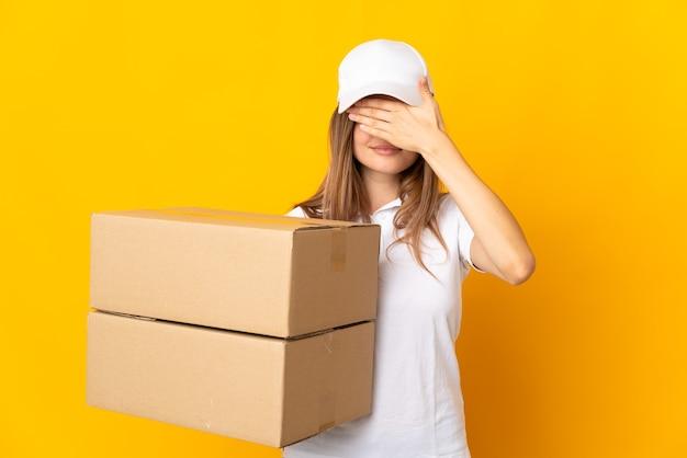Młoda słowacka kobieta dostawy na białym tle na żółtym tle zasłaniając oczy rękami. nie chcę czegoś widzieć