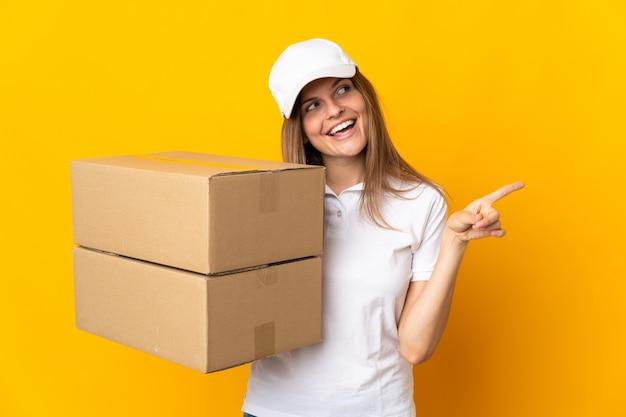 Młoda słowacka kobieta dostawy odizolowana na żółtym tle wskazujący palec w bok i prezentująca produkt