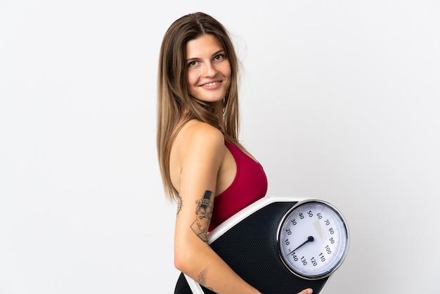 Młoda słowacka kobieta na białym tle na białej ścianie z wagą