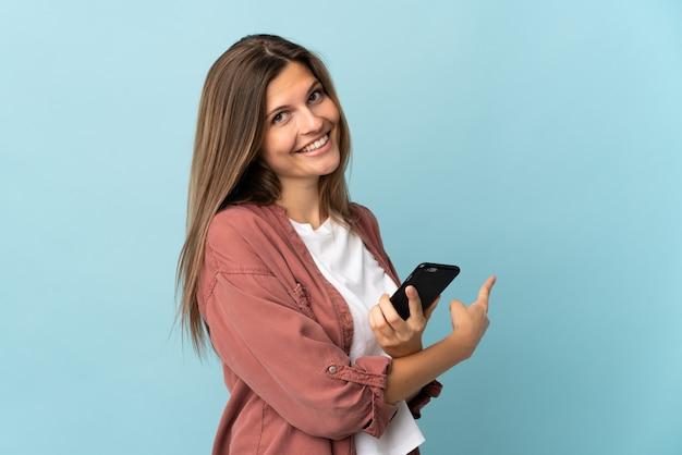 Młoda słowacka kobieta na białym tle przy użyciu telefonu komórkowego i wskazując wstecz